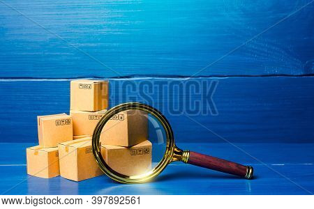 Cardboard Boxes And Magnifying Glass. Concept Of Searching For Goods And Components. Procurement Aud