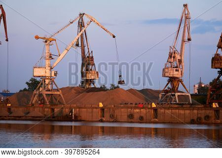 Level-luffing Bulk-handling Cranes Load Sand Onto A Dry Cargo Barge In A River Port In The Evening L