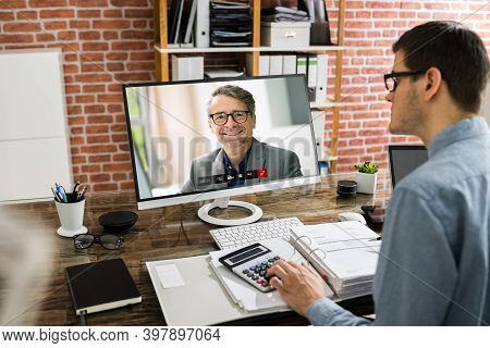 Financial Tax Advisor Looking At Invoice In Video Conference With Client