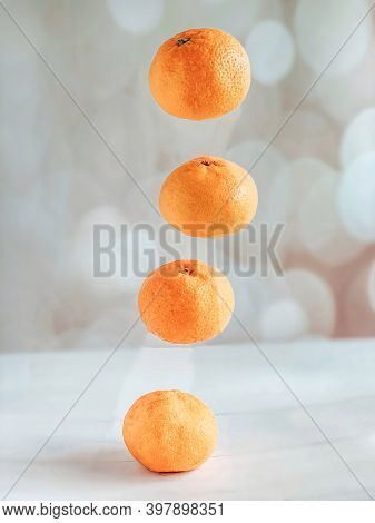 Four Levitating Tangerines On A Beige Background. The Concept Of A Healthy Lifestyle And Nutrition,