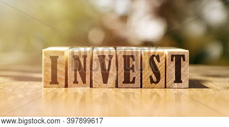 Invest Word On Wooden Cubes. Saving And Investment Business Financial Concept.