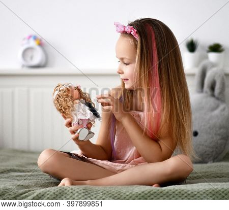 Smiling Pretty Small Girl With Decorative Bow And Pink Strands In Hair Sitting On Bed And Playing Wi