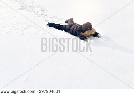 A Child In A Winter Jumpsuit Lies Sprawled In Full Height In The Snow, Face Down.
