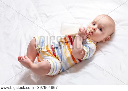 Cute Caucasian Baby With First Baby Milk Bottle. Top View. Artificial Feeding Concept. Baby Milk For