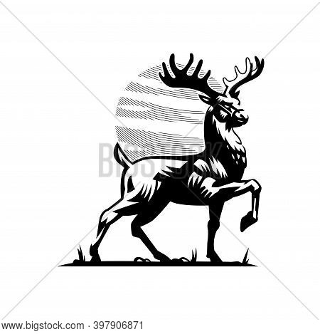 A Deer With Large Horns And A Raised Paw Is Standing On The Grass. Against The Background Of The Sky