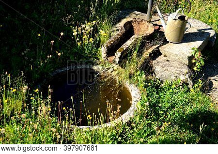 Concrete Circular Cemetery Well In A Meadow With A Source Of Water For Watering