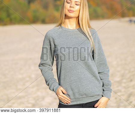 Smiling blond woman with closed eyes standing on beach. She is wearing grey hoodie. Fashion mockup with casual outfit.