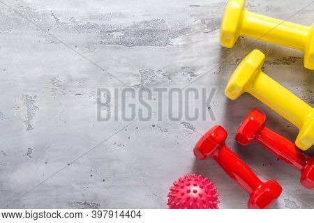 Fitness Background. Equipment For The Gym And Home. Red And Yellow Dumbbells And A Massage Ball On A