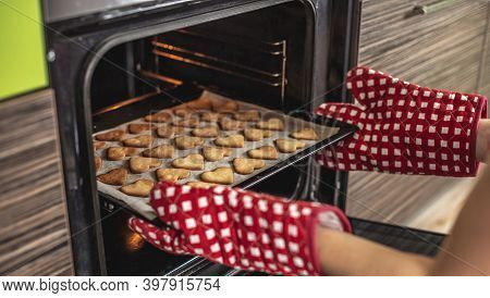 Woman Is Taking Out A Baking Tray With Delicious Homemade Heart-shaped Cookies From The Oven. Concep