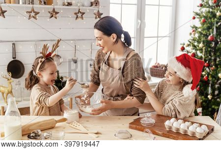 Merry Christmas and Happy Holidays. Family preparation holiday food. Mother and daughters cooking cookies.