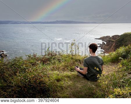 Relaxed guy sitting on the grass meditating