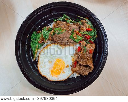 Rice Topped With Stir-fried Beef And Basil With A Fried Egg In The Food Container