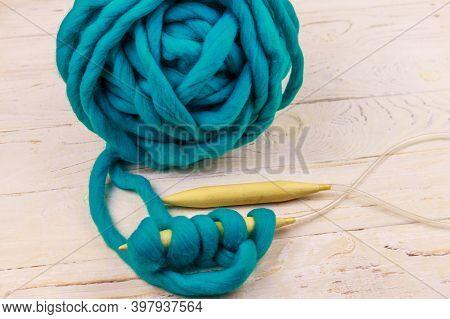 Merino Wool Yarn Ball And Knitting Needles On White Wooden Background