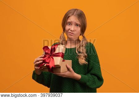 Charming Blonde Girl 12-14 Years Old In Warm Green Sweater Open A Present Box With Red Bow. Studio S