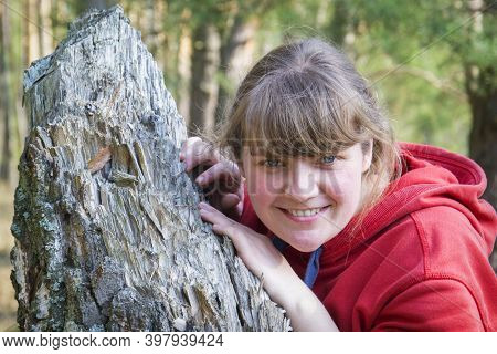 In The Spring In The Forest On A Bright Sunny Day, A Girl Is Leaning On A Tree Trunk. Close-up.