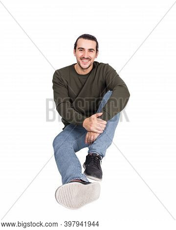 Contented Casual Young Man Sitting On The Floor Smiling To Camera. Lifestyle Full Length Portrait Ha