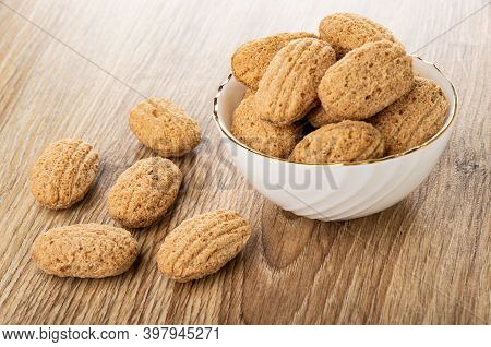 Crispy Oat Pillows With Filling In White Bowl, Few Crispy Pillows On Brown Wooden Table