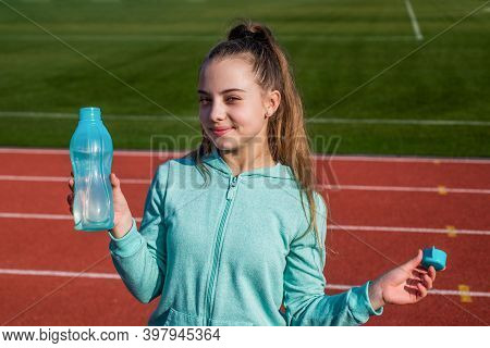 Thirsty And Hydration. Teen Girl Drink Water On Stadium. Kid In Sportswear Relax Outdoor. Child Do E