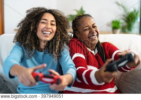 Happy Mother And Daughter Having Fun Playing Video Game At Home - Gaming Entertainment And Technolog