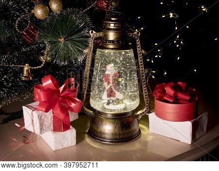 Christmas Magic Lantern With Toy Santa, Gift Boxes With Red Ribbon, New Year Tree On Table In Room.