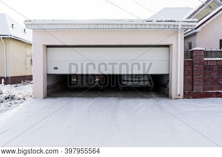 xterior of a  garage attached to a house. garage with two cars inside in winter. semi-open sectional