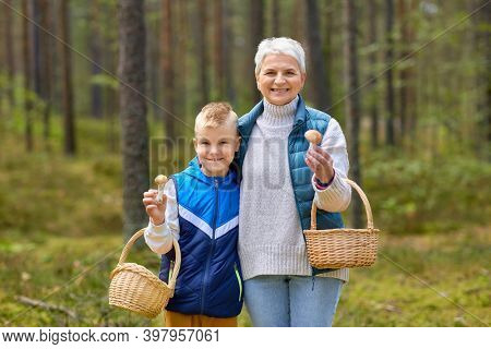 picking season, leisure and people concept - happy smiling grandmother and grandson with baskets and mushrooms in forest