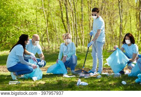 volunteering, health and ecology concept - group of volunteers wearing face protective medical mask for protection from virus disease with garbage bags cleaning area in park