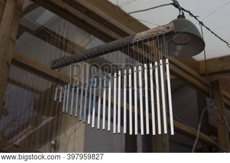 Unique Handmade Wind Chime On House Background.