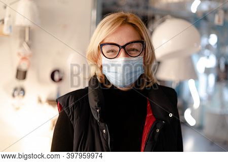 Middle Aged Woman With Medical Mask At Work. Small Business Owner On Quarantine