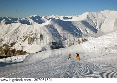 Two Snowboarders Riding On Recently Prepared Snow Piste In Sunny Morning In The Mountains. Copy Spac