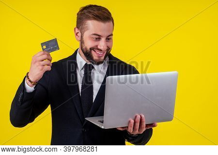 Attractive Excited Young Brunette Man Isolated Over Yellow Background Holding Laptop Computer And Pl