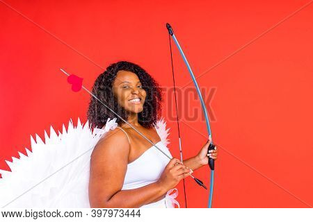 African Latin Cupid Woman In Wtite Top Bra Holding Bow And Arrow In Red Studio The 14th Of February