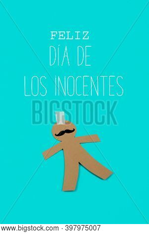 text happy innocents day written in spanish and a paper man, as a prank for the dia de los inocentes, the innocents day, a feast held in spain and hispanic america equivalent to april fools day