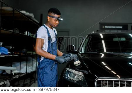 Car Detailing And Polishing Concept. Professional Black Male Car Service Worker In Uniform, Holding