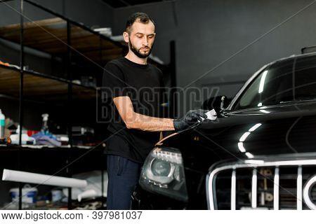 Young Man, Car Polish Service Worker Polishing Car Hood, Buffing And Polishing Vehicle With Nano Cer