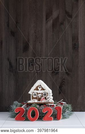 Gingerbread House And Inscription 2021 On Brown Wooden Background. New Year Concept. Copy Space.