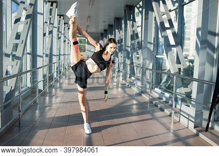 Full Length Portrait Of Muscular Brunette Woman Practicing Split. Young Female Flexible Athlete Posi