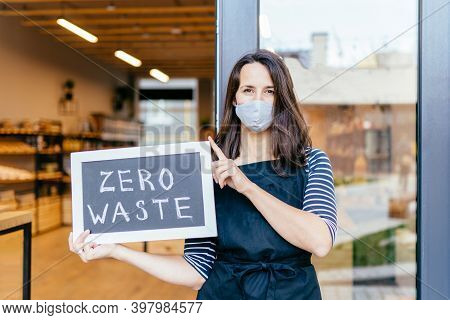Decisive Saleswoman In Apron, Protective Mask, Gloves Holding Zero Waste Sign In Doorway. Female Own