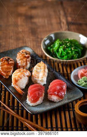 Assortment Of Japanese Sushi Set, Nigiri, Gyozas Dumplings And Wakame Salad In Ceramic Plates With S