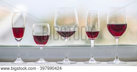 Five different glasses of red wine at window