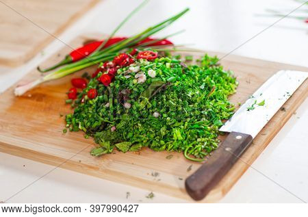 Knife and minced herbs. Green onion, chili pepper on a board