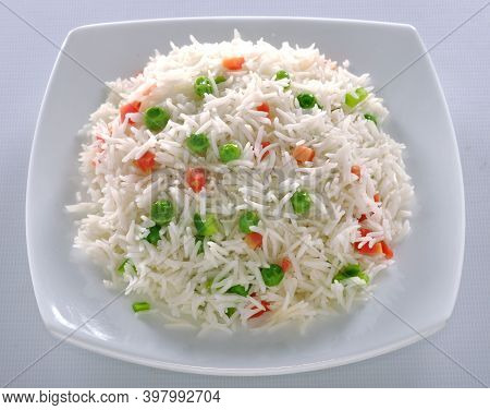 rice with vegetables on  plate isolated on white background . rice with tomatoes, cucumbers and onio