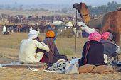 Group of camel traders relaxing at the Pushkar Fair. Rajasthan India poster
