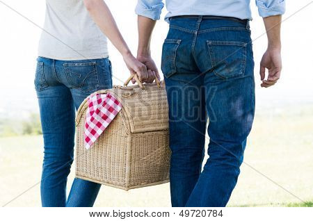 Young Couple Walking Holding Picnic Basket Together