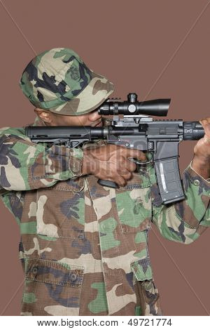 Male US Marine Corps soldier aiming M4 assault rifle over brown background poster