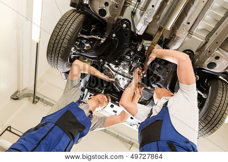 Auto mechanics working underneath a lifted car