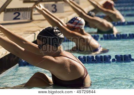 Row of female swimmers holding onto starting block preparing to swim backstroke