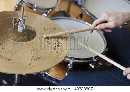 Closeup of hands playing drum set
