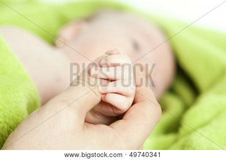 Baby hand gently holding adult's finger  poster