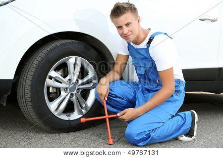 Auto mechanic changing wheel